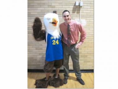 High School of Fashion Industries Principal Daryl Blank poses with the school mascot, the Feagle, a cross between a falcon and eagle.