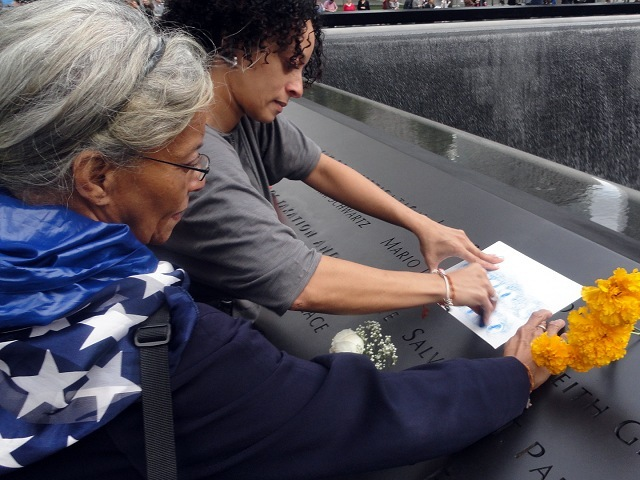 Yesenia L. Rodriguez, 38, of the Lower East Side made a rubbing from the name of childhood friend Mario L. Santoro, an EMT, at the 9/11 Memorial during community day on Oct. 2, 2011. Her mother, Raquel Rodriguez looks on.