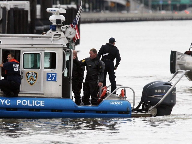 The NYPD searches the East River after a commercial helicopter crash on October 4, 2011 in New York City. A helicopter carrying five people crashed into the East River, the pilot and three passengers have been pulled from the river, a fourth died in the crash.