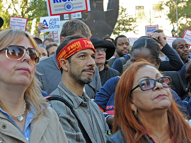 A TWU worker at Foley Square listens to a speaker.