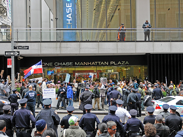 Protesters stop in front of an entrance to One Chase Manhattan Plaza.