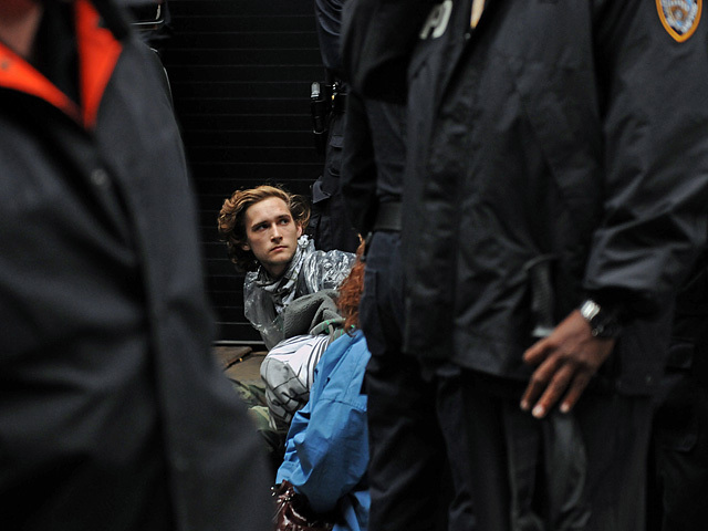 One of the younger protesters sits on the ground after being arrested.