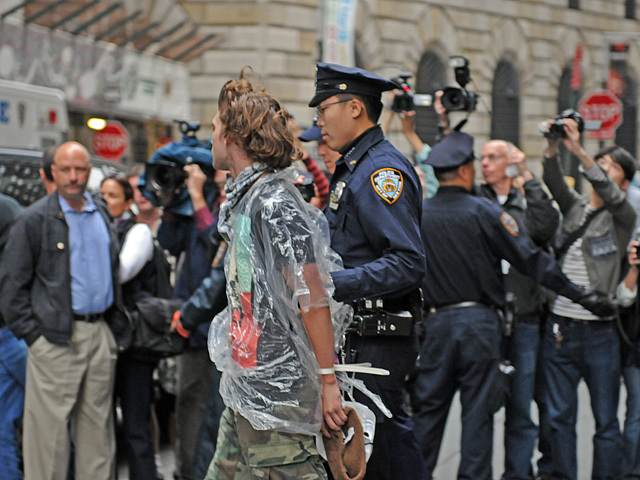 An Occupy Wall Street protester is brought to a police van after being arrested.