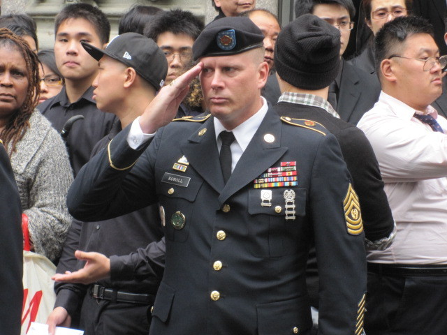 Military personnel saluted during the procession in Chinatown on Thurs., Oct. 13, 2011.