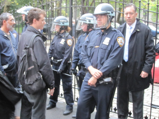 A protester stares down police at the entrance to City Hall on Broadway during an Occupy Wall Street march on Fri., Oct. 14, 2011.