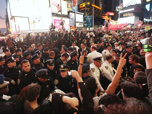 Police attempt to push back demonstrators associated with the 'Occupy Wall Street' movement during a protest in Times Square on October 15, 2011 in New York City. Thousands of people are taking to the streets in cities across the world today in demonstrations inspired by the 'Occupy Wall Street' protests against the global financial system that began here in New York.