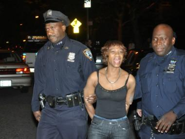 Sean Hines' mother, Yvonne, is led away from their home at 92nd Street and Columbus Avenue in cuffs. Hines was murdered there on Oct. 14, 2011.