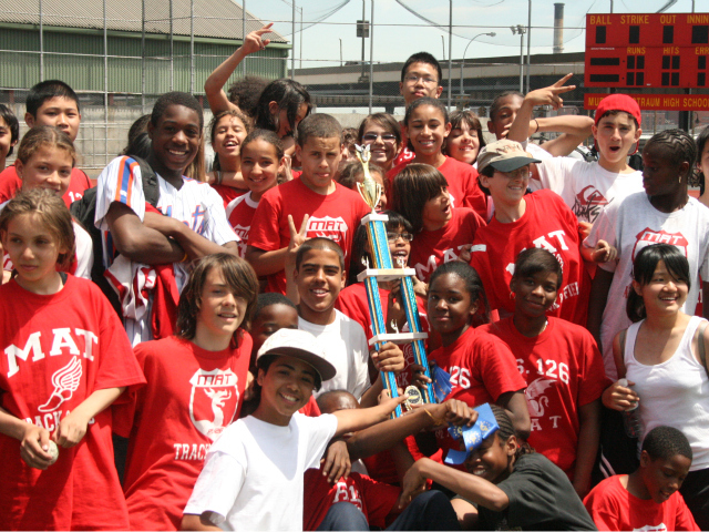 The track team at the Manhattan Academy of Technology celebrated a trophy. The school is one of many across the city that is now facing cuts to its coaching funding.