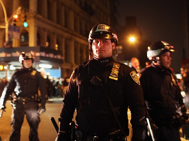 Police keep watch over Occupy Wall Street protesters following arrests during a demonstration to show support for their counterparts in Oakland, California on October 26, 2011 in New York City. Police fired tear gas into a crowd of hundreds of protesters associated with the Occupy Oakland movement last night following their eviction from a local park.