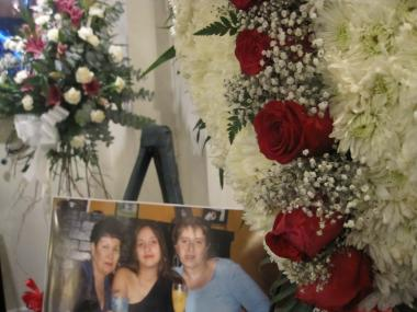 Flowers and a photo of 73-year-old Julia Hernandez (far left) with her granddaughter Jasminda Otero and daughter Elaine Hernandez.