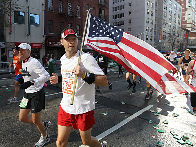 <p>A runner flies the American flag during this years NYC Marathon.</p>