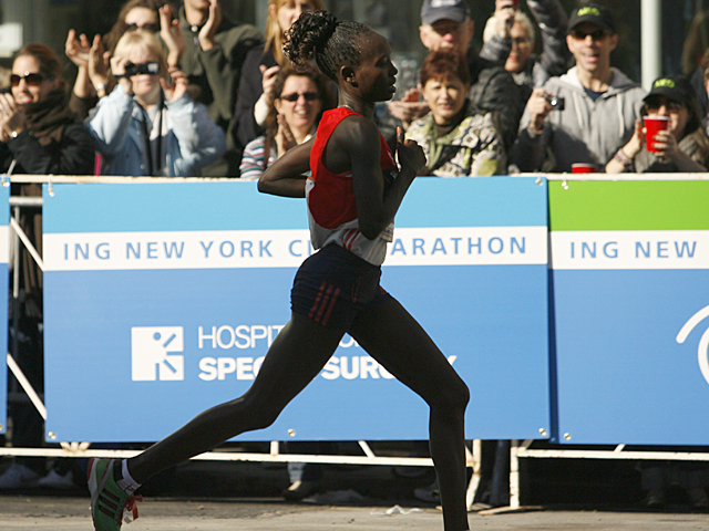 <p>A runner passes the cheering crowd during the NYC Marathon.</p>