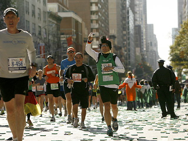 <p>A runner captures another memory during the 2011 NYC Marathon.</p>