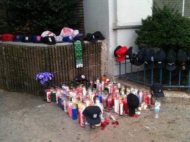Candles and baseball caps form a memorial for Reggie Andrews, 22, who was killed on his birthday outside his home at 111th Street and Lenox Avenue on Nov. 12, 2011.