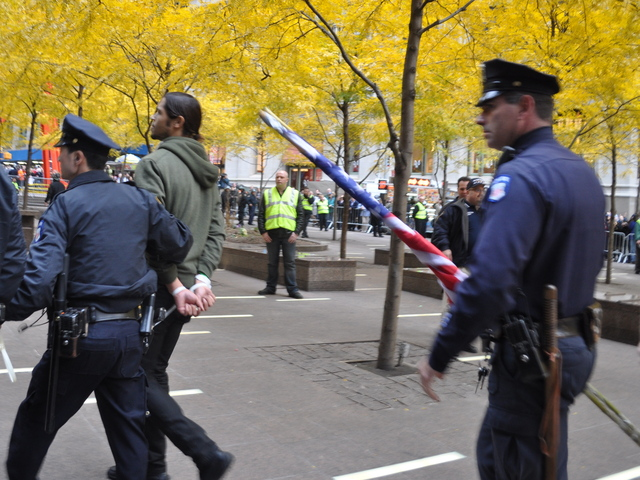 A man jumped the fence and ran into Zuccotti Park to retrieve an American flag, after the park had been cleared, and was arrested by police.
