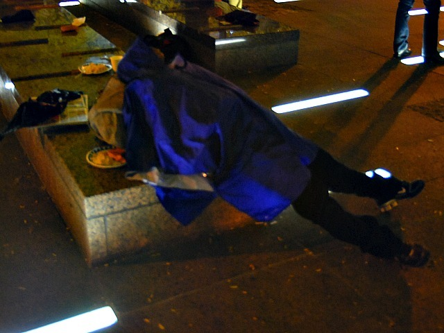 An Occupy Wall Street protester draped in a coat sleeps hanging off a bench at Zuccotti Park the night after the plaza was cleaned on Nov. 15, 2011.