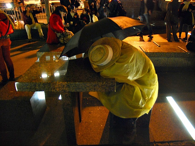 An Occupy Wall Street protester in rain gear sleeps standing up in Zuccotti Park the night after the plaza was cleaned on Nov. 15, 2011.