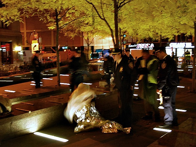 Cops rouse an Occupy Wall Street protester sleeping in a foil blanket at Zuccotti Park on Nov. 15, 2011 after the park was cleaned.