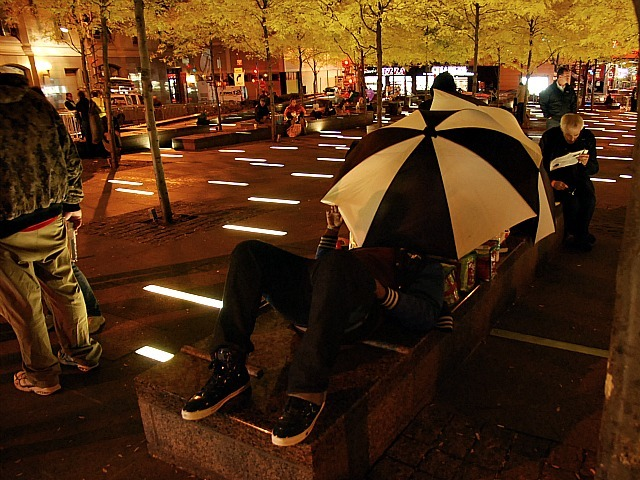 An Occupy Wall Street protester sleeps under an umbrella in Zuccotti Park on Nov. 15, 2011 after the plaza was cleaned.