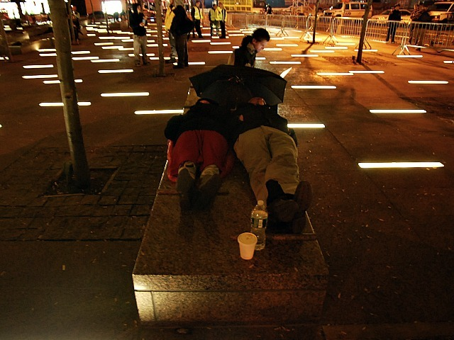 Occupy Wall Street protesters sleep on a bench in Zuccotti Park on Nov. 15, 2011 after the plaza was cleaned.