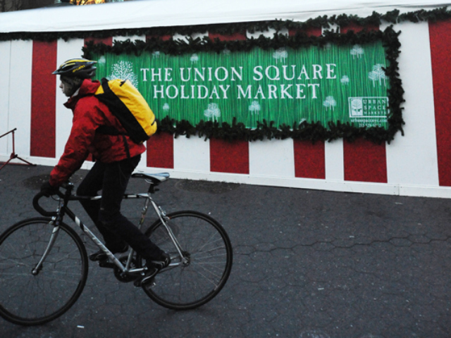 <p>A man rides by the Union Square Holiday Market.</p>