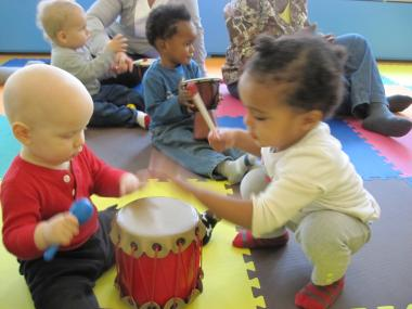 Baby Rowan and Aklil share a drum in Kidberry's music class.