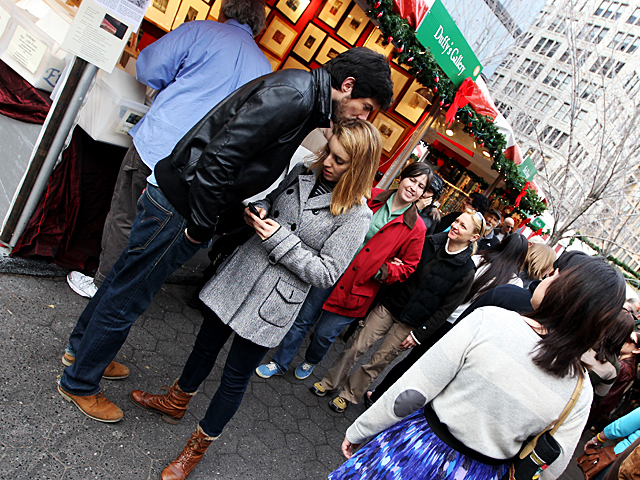 <p>A couple finds time for romance during their holiday shopping at the Union Square Holiday Market on Nov. 27, 2011.</p>