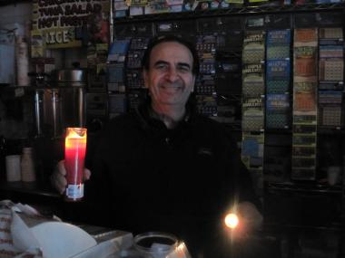 Andrew Floratos holds up the flashlight and candle he's been using to help customers peruse merchandise.