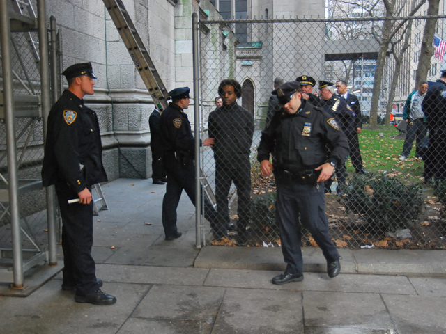 Police keep a man in handcuffs after he scaled scaffolding at St. Patrick's Cathedral on Dec. 5, 2011.