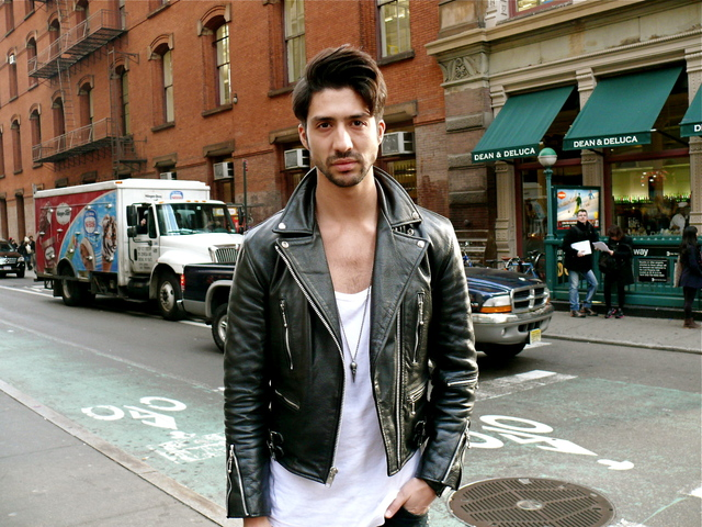 Daniel B. in a classic style biker jacket, with a wide necked t-shirt and volume brushed hair.