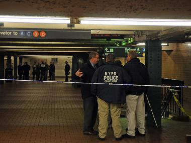 Cops investigate a police-involved shooting at the 125th Street D train station on Dec. 9, 2011.