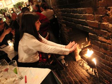 Jennifer Logue warms herself by the fire at the Tavern on Jane in the West Village.
