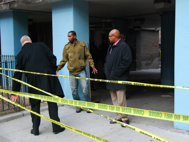 NYPD detectives question a friend of a victim in a murder-suicide on Dec. 12, 2011.
