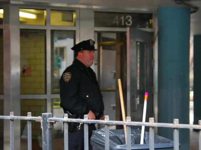 An officer stands outside of the entrance to the crime scene at the Fulton Houses on Dec. 12, 2011.