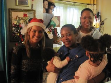 Harlem YMCA Executive director Tffeny Forrest (back row) delivered presents to Taisheba Smith and her young family of three kids along with Karen Sprauer, site director of the YMCA's afterschool program at P.S. 57
