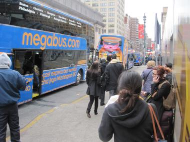 Passengers crowd the sidewalk at a Megabus stop, Dec. 20, 2011.