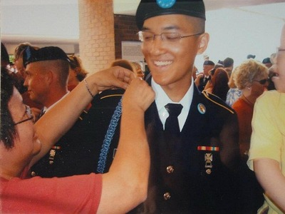 <p>Pvt. Danny Chen&#39;s mom fixes his shoulder cord in Ft. Benning, GA.</p>
