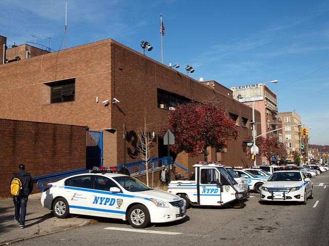 A police car double parks outside the 34th Precinct.