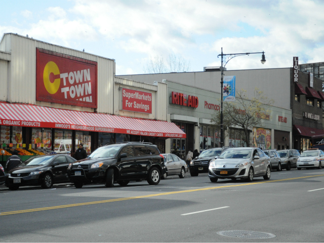 A black SUV double parked outside C-Town in Inwood as a traffic police car approaches. The driver of the car returned to the empty vehicle and moved before being towed.
