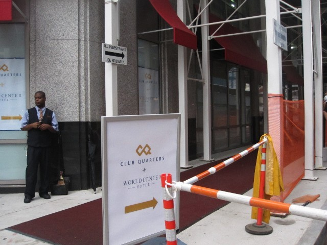 A bellhop waits to escort guests along a red carpet beneath a sidewalk shed to the hotel's entrance.