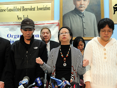 <p>OCA-NY president Elizabeth OuYang (at center), flanked by the parents of Army Pvt. Danny Chen, at a press conference in Chinatown on Thurs., Jan. 5, 2012.</p>