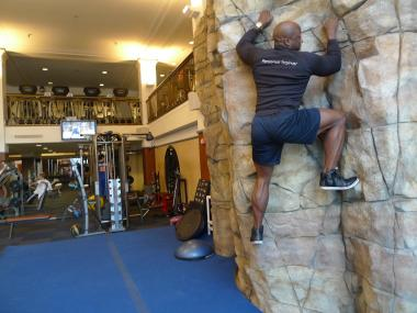 Kali O'Mard, manager of fitness services at New York Health & Racquet Club, demonstrates the bouldering wall at the club's Cooper Square location.