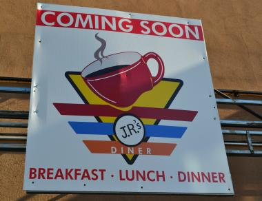 A sign for J.R.'s Diner, set to open at Cooper and Metropolitan Aves. in Glendale, shows a steaming cup of coffee.