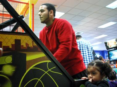 Arnaldo Santiago, 19, shoots arcade hoops while daughter Anayalee, 3, looks on.