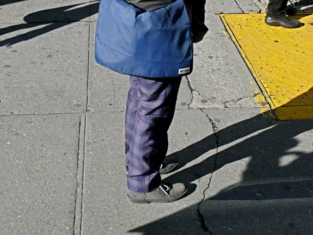 Very tailored purple tartan with a Jack Spade nylon jacket and gray Chukka boots on a female pedestrian on 14th Street, West Village.
