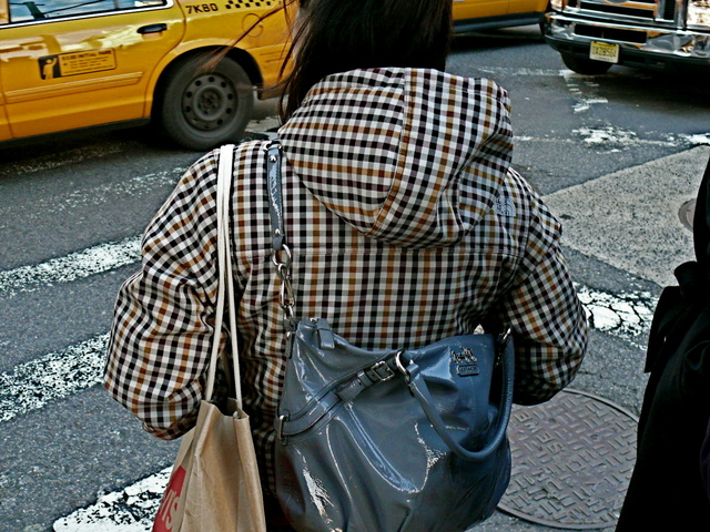 Nylon check hoodie jacket and contrasting patent leather shoulder bag on Broadway in SoHo.