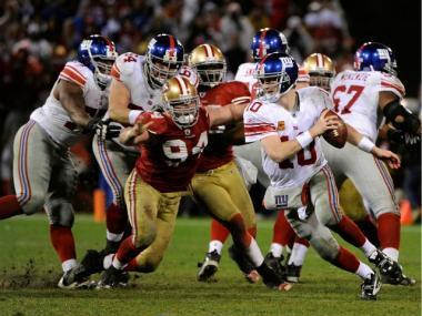 Eli Manning #10 of the New York Giants attempts to avoid pressure from Justin Smith #94 of the San Francisco 49ers during the NFC Championship Game at Candlestick Park on January 22, 2012 in San Francisco, California.