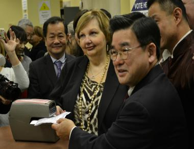 Councilman Peter Koo (right) switches from the Republican to Democratic parties at the Board of Elections office in Kew Gardens.