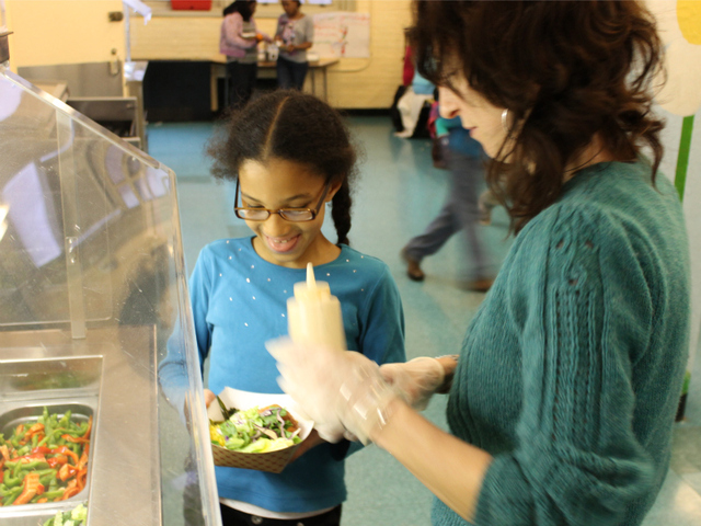 <p>P.S. 11 parent volunteer Matilda Brooker gives some vegetables from the school&#39;s salad bar to Emma, 9.</p>