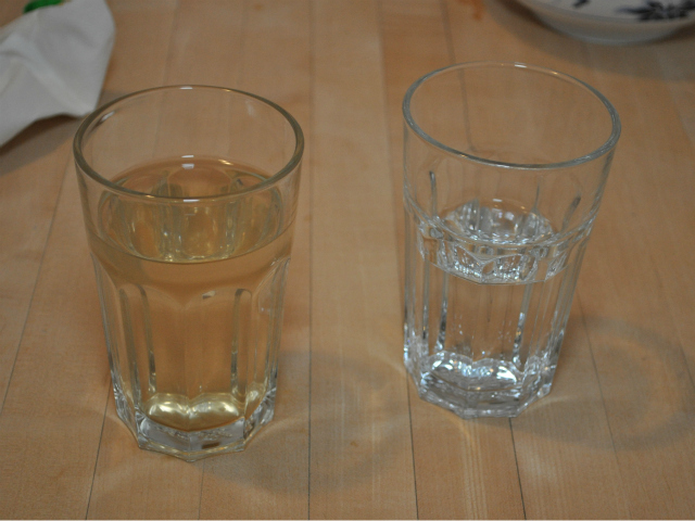 A side-by-side comparison of water samples from the Keithley home. To the left, a glass of brown water from the faucet. To the right, a glass of distilled water.
